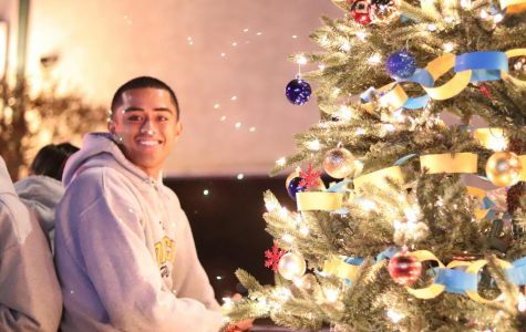 Fano Maui from the Oil Tech program sits next to the Christmas tree and smiles for the camera.