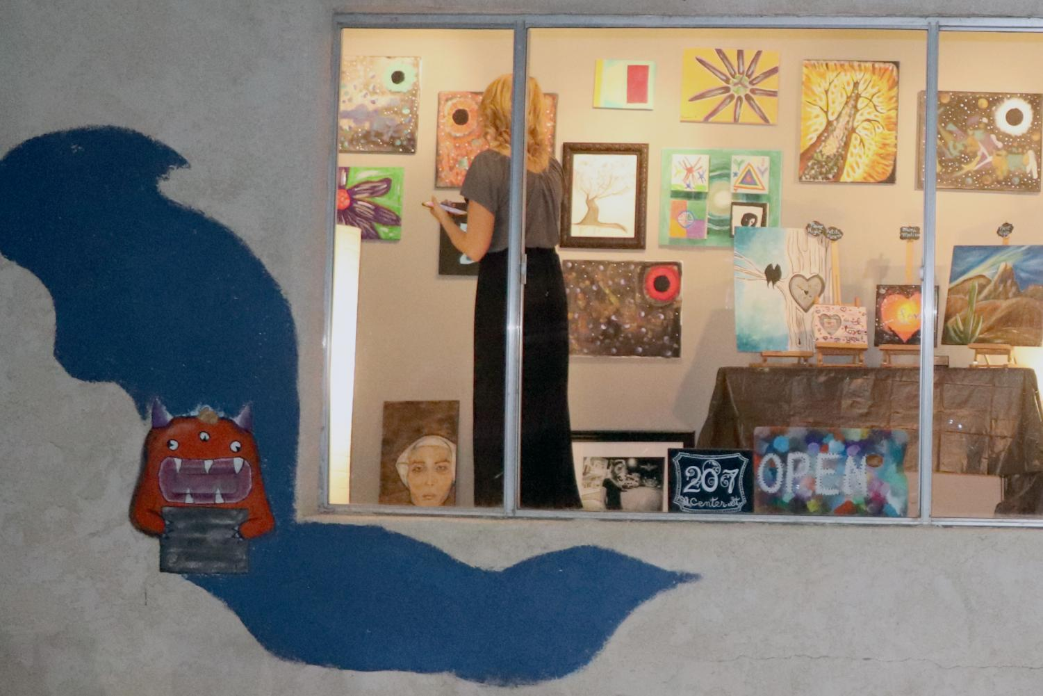 From outside the art show, a patron views the students' work.