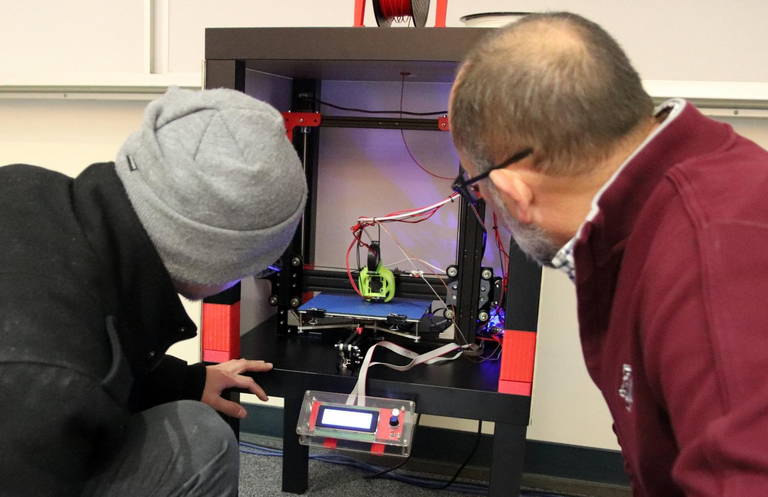 Eduardo Morales showing Ted Pendergrass how his 3-D printer works.
