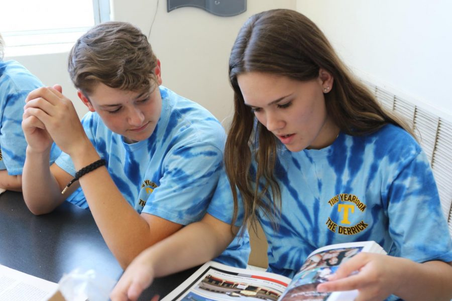 Hunter Everson and Jaden Shafer look through the yearbook as they distribute them to eager seniors.