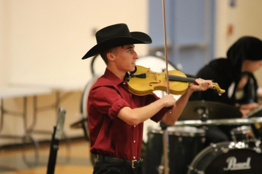 Dawson Lopez playing the violin while dressed as the Devil.