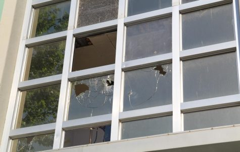 Vandalized windows in front of the science building on Wildcat Way.