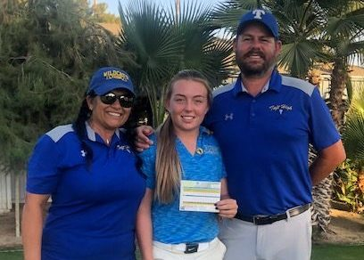 Macayla Wells shows off her scorecard with coaches Charlotte Kidd and Mike Cowan.