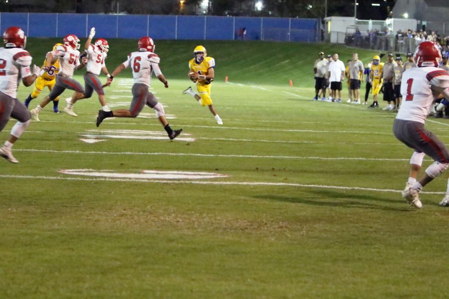 Quarterback Nick Vargas scrambling in the pocket looking for an open receiver. He made his way toward the left sideline in order to avoid crossing the line of scrimmage.