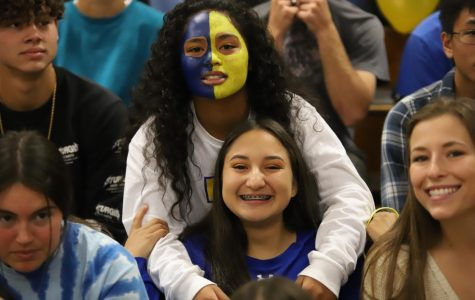 (Mariah Nevarez) Alana Iotamo and Adrianna Ramos smile for a photo at the homecoming rally. Alana showing off her school spirit with her gold and blue face. Adrianna with her blue braces and blue long sleeve shirt.