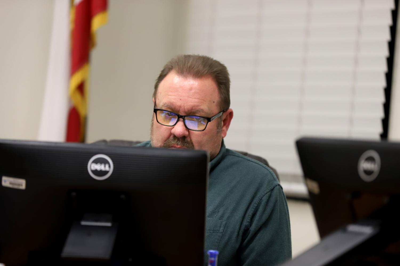 Board member John Kopp at the January 22 board meeting. Kopp seeming focused on the meeting as he looks over the board agenda.