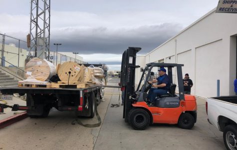 MOT employees unloading a truck while using a forklift.