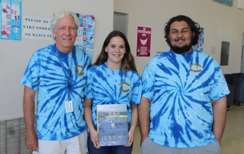 2018 Adviser Jim Carnal, Co-editor Hunter Everson, and co-editor Carlos Margis show off the yearbook cover at the yearbook dedication and distribution last May.