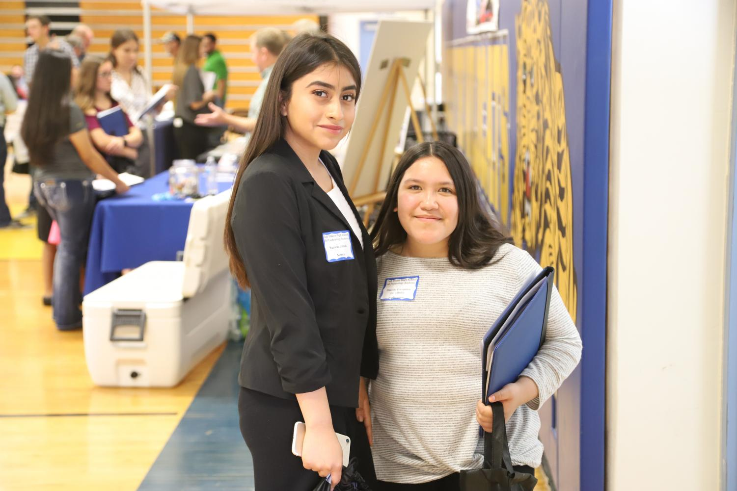 Oil Tech students (on left) Pamela Galindo and Daniela Cervantes (on right) walk around the gym and interview companies.