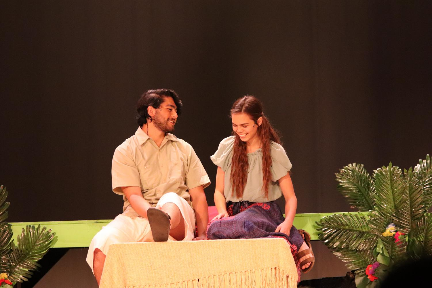 Daniel Beauxhomme (Eulysses Urrea) and Ti Moune (Kenya Orsburn) sitting and talking with each other.