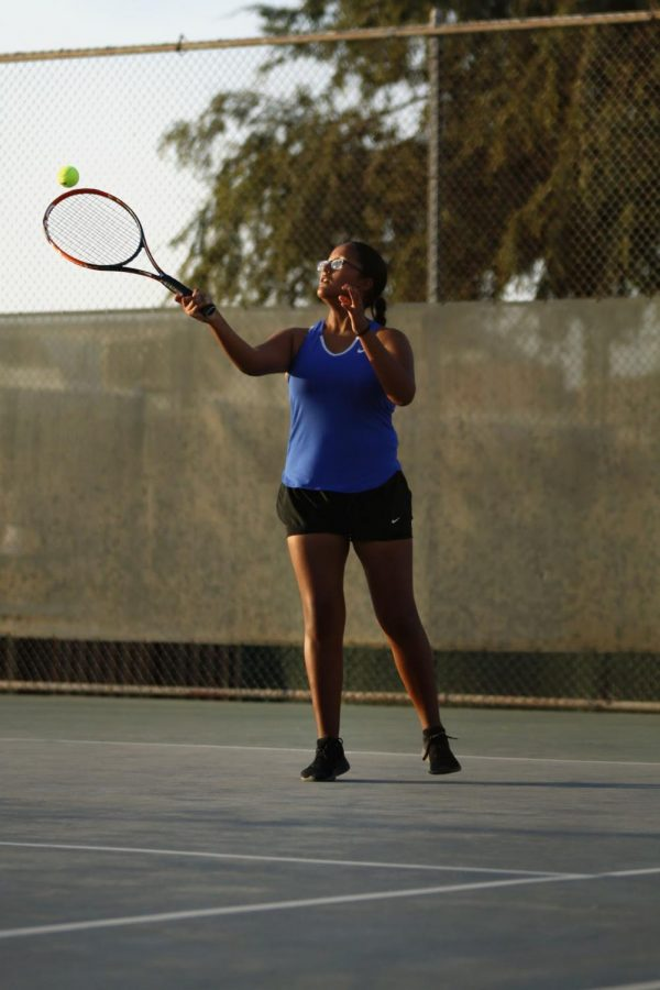 Cristal Martinez-Munoz is hitting a forehand out of the air during her singles match.