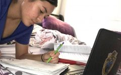Miriam Guzman is shown writing down notes for her classes. Guzman said her favorite thing about online school is,